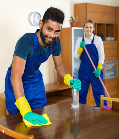 dusting: Positive smiling cleaners cleaning and dusting in ordinary house