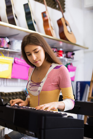 synthesiser: Young girl selecting control keyboard for synthesiser in shop