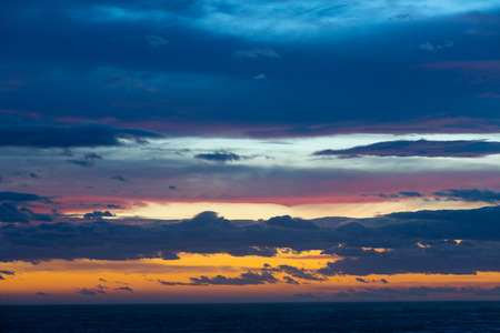 Sky scenery with cloud breaks above still ocean