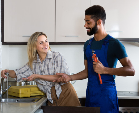 unblock: Young African plumber and happy white housewife at apartment Stock Photo