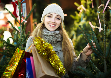 lifestile: Smiling young woman inspecting fir-trees at Christmas market  in evening