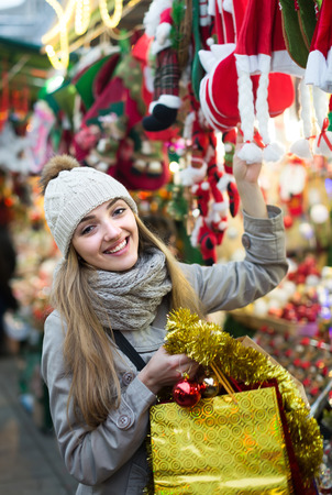 overspending: Portrait of smiling female customer near counter with Christmas gifts in evening time Stock Photo