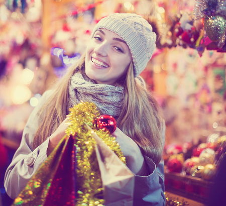 Pretty  girl in coat posing at Xmas market  in evening Stock Photo