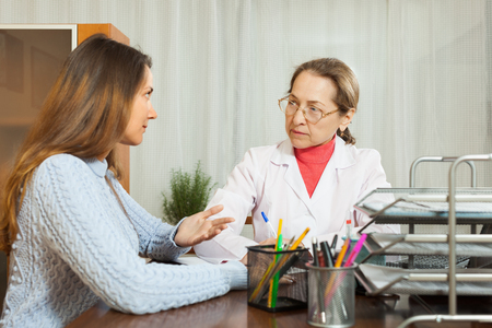 malaise: Sick girl complaining  to doctor about symptoms of malaise Stock Photo