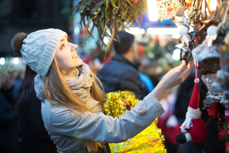 overspending: Portrait of positive girl shopping at festive fair before Xmas in evening time Stock Photo