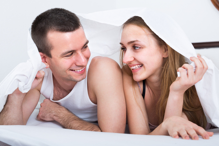 bed sheet: Young girl and man posing in bed covered with sheet Stock Photo