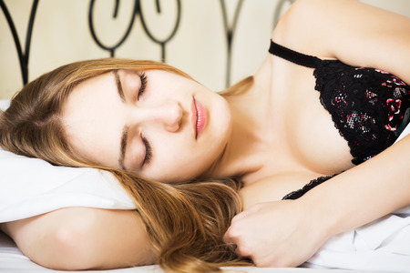 early twenties: Seductive brunette girl sleeping on white pillow in bed in home interior
