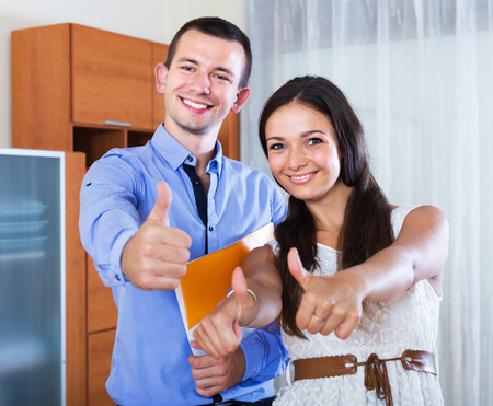 fiance: Young couple filling marriage application form and smiling. Focus on man