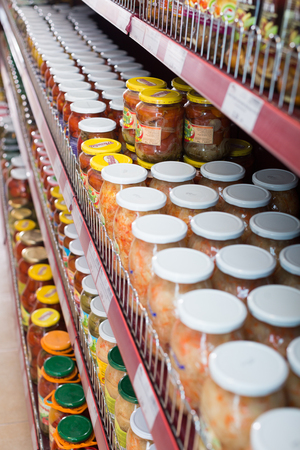 tinned goods: BARCELONA, SPAIN - FEBRUARY 02, 2016: Display with ordinary assortment of glass food products and marinated vegetables  in East European food store Editorial