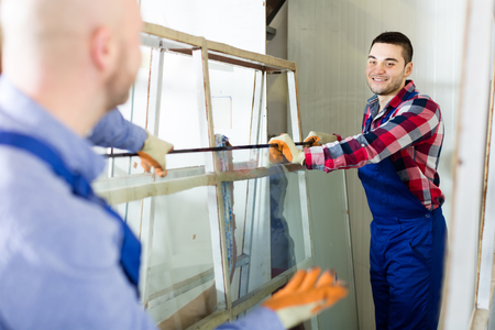 Smiling production workers in coverall working with different PVC window Stock Photo
