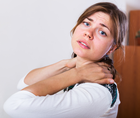 muscle spasm: Young woman stretching stiff neck and feeling pain in home interior