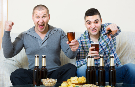 Two excited male sport fans watching hockey game with beer heatedly at home Stock Photo
