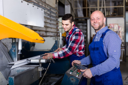 enginery: Couple of people near milling machine at factory
