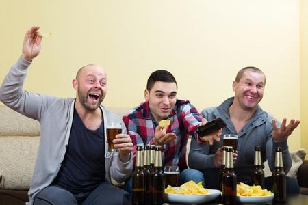 fandom: Three male sport fans watching hockey game heatedly indoor