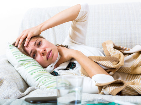 Portrait unhappy woman suffering of sore throat and fever at home Stock Photo