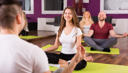 learners: Coach showing to adult learners new yoga posture indoor Stock Photo
