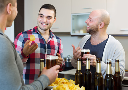 bout: Three happy smiling male friends with glasses of beer and chips indoor