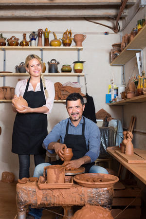 artisans: Two smiling artisans in ceramics workroom with pottery wheel and various clay vessels