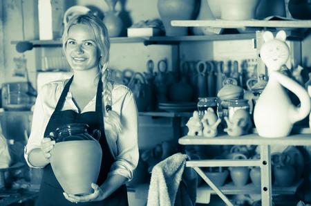 alfarero: Smiling woman potter in apron carrying ceramic vessels in atelier Foto de archivo