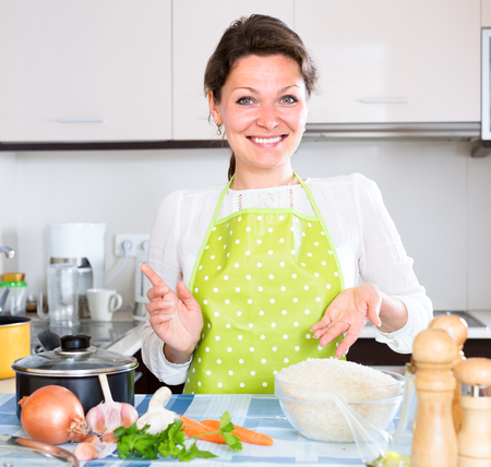 hypothec: Portrait of beautiful smiling woman standing near the table in a modern kitchen Stock Photo