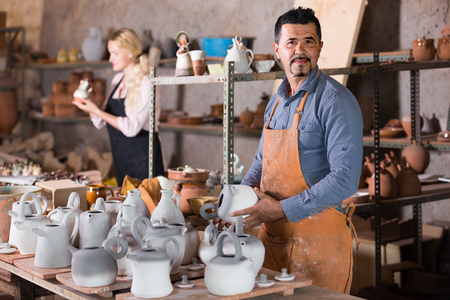 glad man potter holding ceramic vessels in atelier