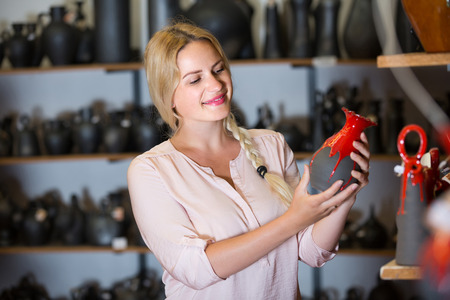 spanish woman: Smiling young spanish  woman selecting ceramics with red enamel in atelier Stock Photo