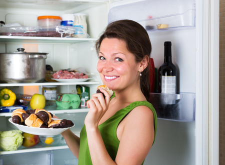woman eating cake: Happy young woman eating cake from fridge  at home
