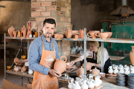 faience: Smiling american man potter holding ceramic vessels in atelier