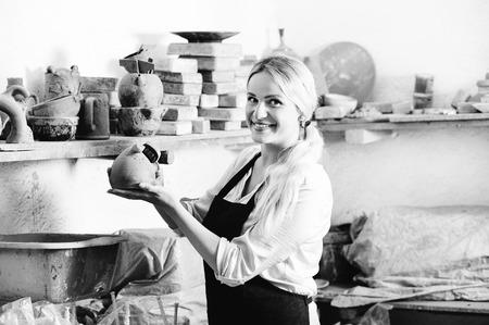 diligente: Retrato de mujer contenta sonriendo trabajador de la cer�mica diligente con vajilla de cer�mica en las manos en el estudio