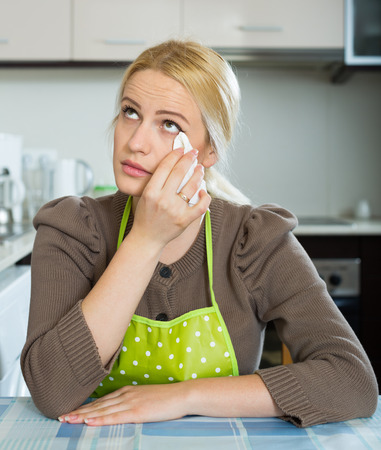 solter�a: Lonely young blonde woman sitting sad at the table at home kitchen