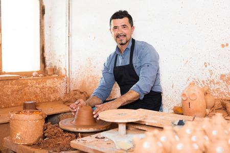 Happy senior man making pot using pottery wheel in studio