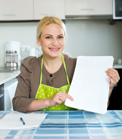 Smiling woman with paper at home kitchen