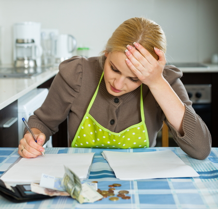 Sad housewife filling in utility payments bills at  home