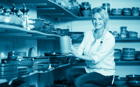 faience: cheerful female customer picking crockery in ceramics workshop