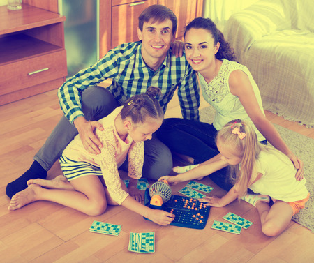 chances: Beautiful little girls with parents trying chances at lotto game. Focus on the little girls