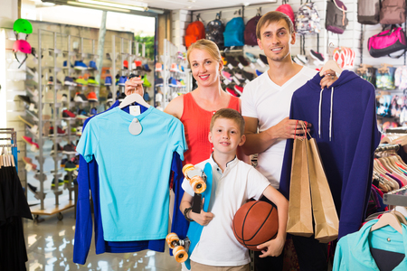 children clothing: Smiling parents with boy in school age shopping clothing in sport store
