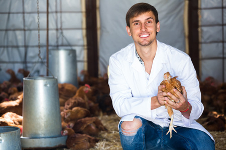 house coat: smiling young man in white coat having chicken in hands in hen house Stock Photo