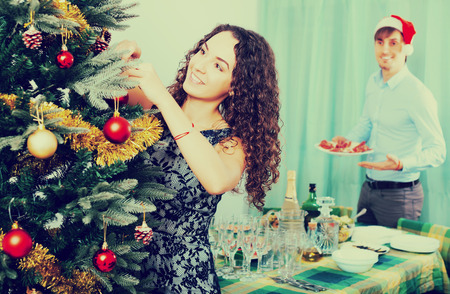 Happy adult couple decorating Christmas tree and serving  festive table in home