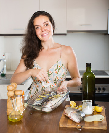 fryingpan: Happy woman cooking fish with ingredient at home kitchen