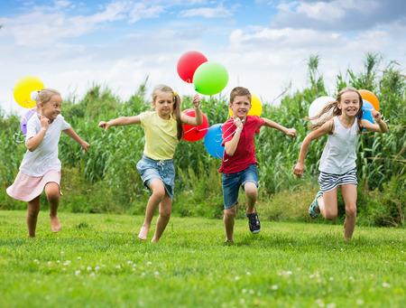 I bambini laught e giocare nei giochi con palloncini multicolori nel parco per il tempo libero