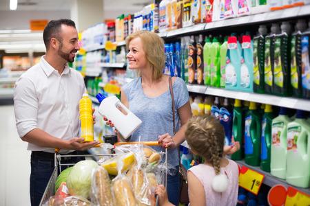 household goods: cheerful family shopping household goods in supermarket