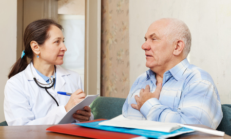 friendly mature doctor talks with sick senior man at near table Stock Photo