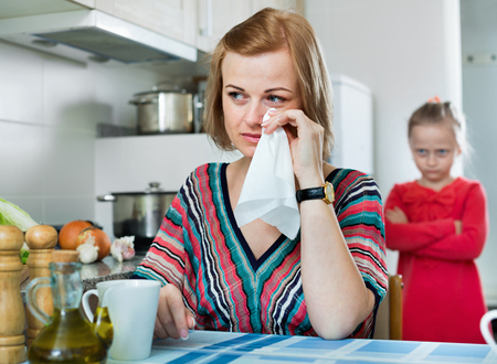 Upset little girl and  young mother have a peeve on each other in the kitchen Stock Photo
