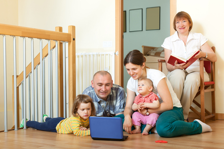 multigeneration: Happy multigeneration family together laptop at home on the floor
