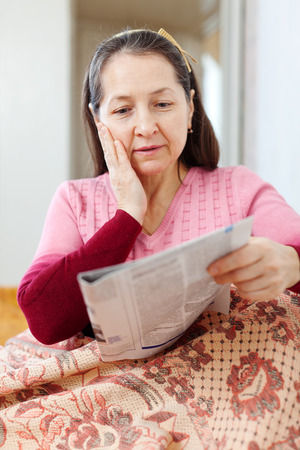 mature woman having sad after readed news in newspaper