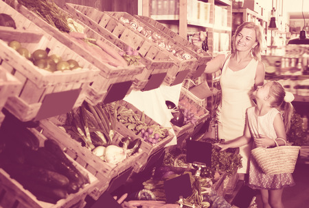 gladly: Portrait of glad adult woman and girl gladly shopping in supermarket