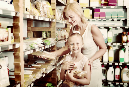 gladly: Portrait of happy young woman and  cute cheerful girl gladly shopping different kinds of pasta in supermarket Stock Photo