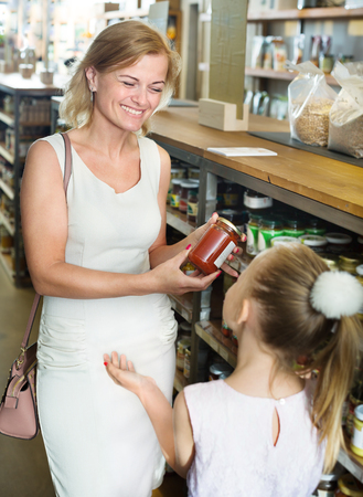 Glad young mother with daughter shopping conserve crushed tomatoes in groceries