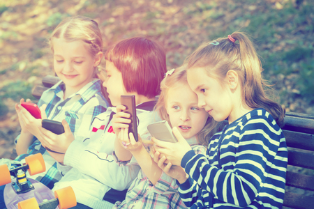 Happy children sitting on bench and playing with mobile devices
