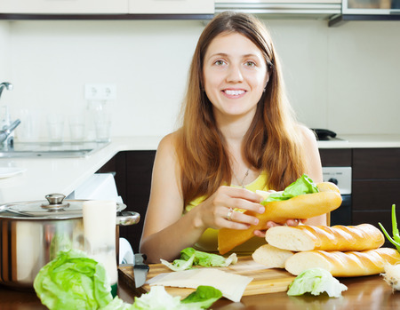 Happy woman cooking sandwiches with cheese and lettuce in her kitchen
